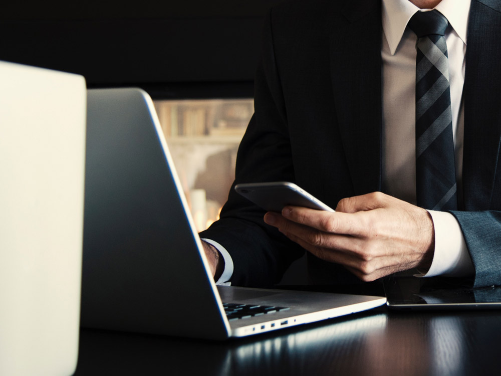Business man using iphone and macbook
